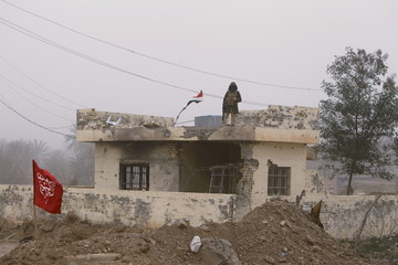 Iraqi Shi'ite fighter stands guard on top of a building on the outskirts of Diyala province, north of Baghdad