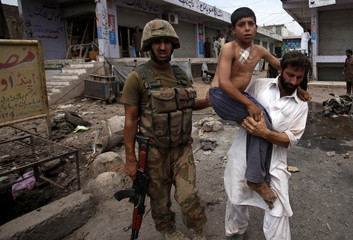 A security official carries a boy who was injured in a bomb attack from the site in the outskirts of Peshawar