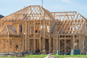 New stick built home under construction, blue sky in Texas, US. Framing structure/wood frame of wooden houses/home. House construction and real estate concept background. Pile of sand, gravel in front