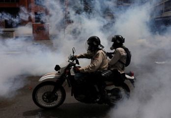 Riot security forces ride a dirt bike while clashing with demonstrators rallying against President Nicolas Maduro in Caracas