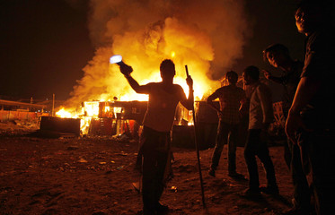A man gestures for people to stay away as a fire burns in a slum in Mumbai