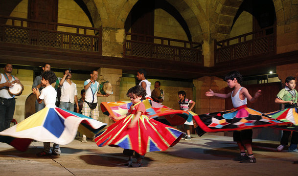 Children practise dancing as whirling dervishes during a class at a performing arts theatre in Cairo