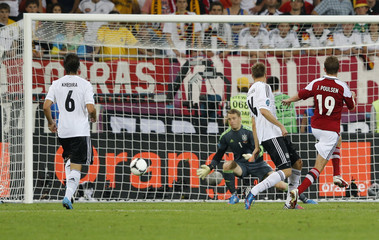 Denmark's Poulsen fails to score against Germany's Neuer as Khedira and Badstuber run up during their Euro 2012 Group B soccer match at the New Lviv stadium in Lviv