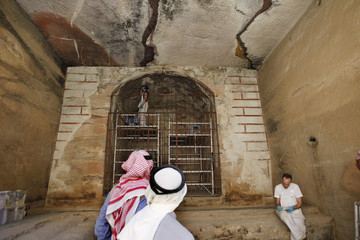 Bedouins watch British conservation specialists restore 2,000-year-old Hellenistic-style wall paintings in a cave complex at Siq al-Barid in Beidha