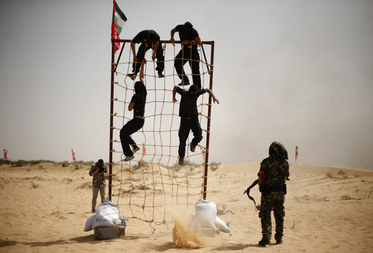 Palestinian militants of the Popular Front for the Liberation of Palestine climb a rope ladder as another shoots at a demonstration during a military graduation ceremony in Khan Younis