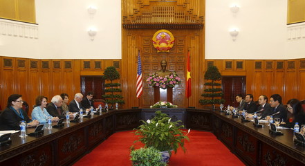 U.S. Democratic Leader, Representative Nancy Pelosi (D-CA) (2nd L) and Vietnam's Deputy Prime Minister and Foreign Minister Pham Binh Minh (2nd R) talk at the Government Office in Hanoi
