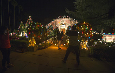People stop to take pictures outside the Balian Ice Cream House which is decorated for Christmas in Altadena