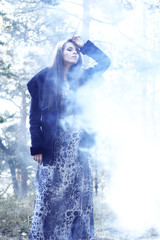 fine art photo. young beautiful woman in mysterious smoke forest