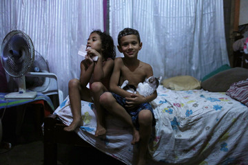 Lucas and sister Lorena pose for the photo at their makeshift home at the Nova Tuffy slum in an abandoned factory in Rio de Janeiro