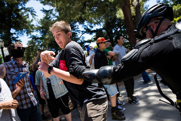 """A police officer grabs a man antagonizing """"anti-fascist"""" protestors after multiple people were stabbed during a clash between neo-Nazis holding a permitted rally and counter-protestors on Sunday at the state capitol in Sacramento."""