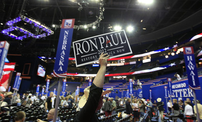 A Ron Paul supporter walks the floor of the Republican National Convention during the opening session in Tampa