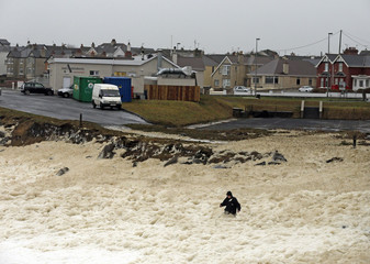 A man walks through sea foam created by storms, in the town of Portstewart on the Irish Coast