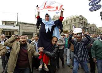 A protester lifts another as they chant anti-government slogans during mass demonstrations against Egypt's President Mubarak in Alexandria