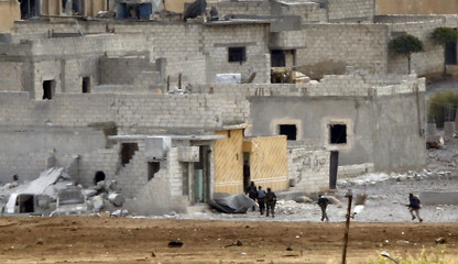 Unidentified armed men run in the Syrian town of Kobani, as seen from near the Mursitpinar border crossing on the Turkish-Syrian border