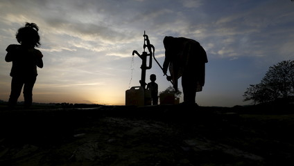 A woman draws water from a well in a slum on the outskirts of Islamabad
