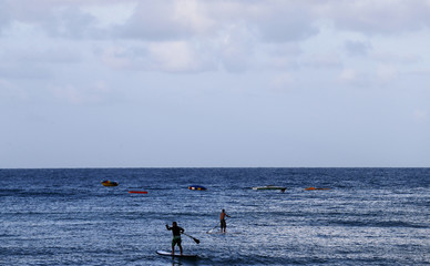 People paddle out from the shores of Ponta Negra beach in Natal