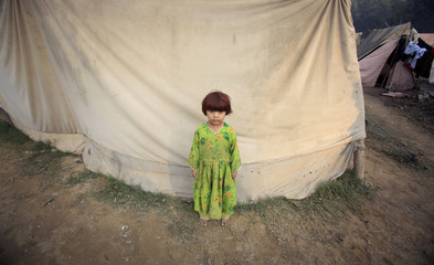Robina, a three-year-old flood victim, stands outside her family tent at a camp for the Internally displaced in Nowshera northwest Pakistan