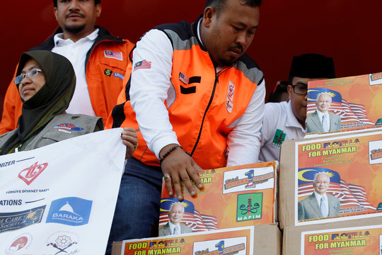 Crew of Malaysian NGO's aid ship carrying food and emergency supplies for Rohingya Muslims display boxes while arrives at the port in Yangon