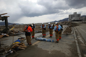 Rescue workers pay their final respects to a dead body retrieved from the rubble in Rikuzentakat, after an earthquake and tsunami