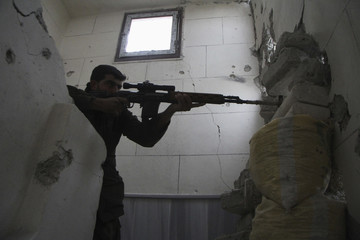 A Free Syrian Army fighter aims weapon as he takes position in Aleppo's Karm al-Jabal district