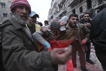 Men help a wounded person after a missile hit Aleppo's al-Mashhad district
