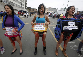 Women, with their bodies painted with blood, hold signs during a protest near the Attorney General's Office in Lima