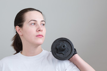 Woman holds a hard dumbbell in the hand. Close up black  dumbbell