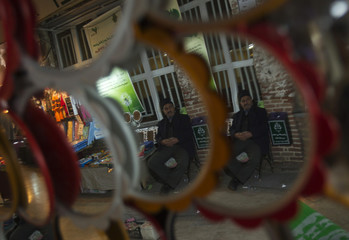 A reflection of an Iranian vendor is seen as he sits beside a stall at the old traditional bazaar in Orumieh, 946 km (587 miles) northwest of Tehran