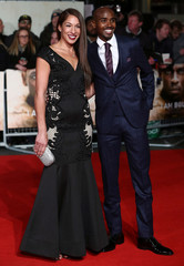 """Athlete Mo Farah (R) and his wife Tania pose for photographers at the world premiere of the film """"I am Bolt"""" in London"""