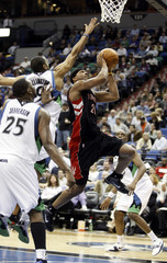 Raptors' Wright drives for a layup past Timberwolves' Ellington and Jefferson during their NBA basketball game in Minneapolis