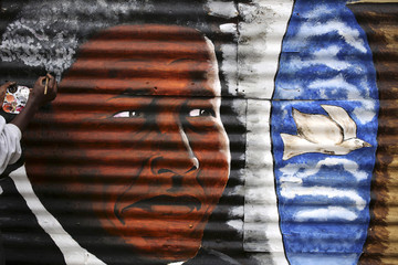 Artist Siya Mbola paints a mural of former South African president Nelson Mandela in Soweto