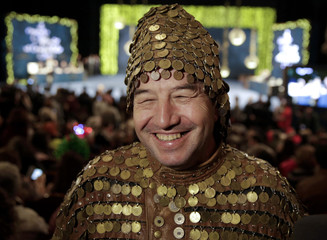 """A man dressed in a costume smiles as he attends the draw of Spain's Christmas Lottery """"El Gordo"""" in Madrid"""