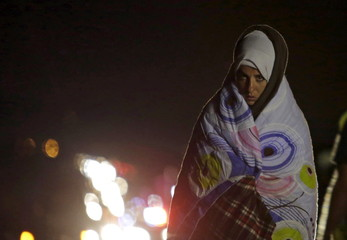 A migrant covers herself with a blanket as it rains, while waiting for buses bound for Austria and Germany, along the M1 highway near Budapest, Hungary
