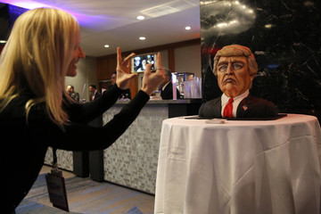 A supporter takes a picture of a cake in the form of Republican U.S. presidential nominee Donald Trump at election night rally in New York