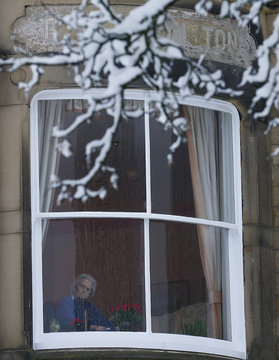 A woman looks out of the window of a residential home after snowfall in Buxton, central England