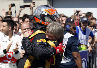 Lotus F1 Formula One driver Grosjean hugs a crew member after the Canadian F1 Grand Prix at the Circuit Gilles Villeneuve in Montreal