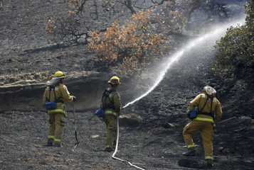 Firefighters douse a hot spot while battling the Wragg Fire near Lake Berryessa