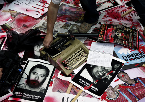 A man puts a pen on a notebook as other tools used by journalists, magazines, newspapers and pictures of slain and missing journalists are placed on a street after a march in Mexico City