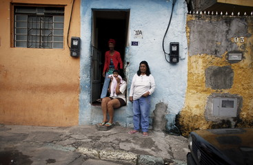 Residents stand in the entrance of a house during inspection of houses at the Limao neighborhood, in Sao Paulo