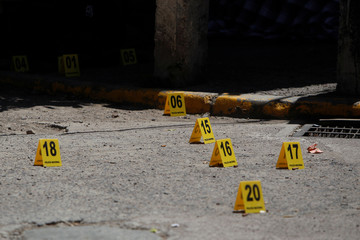Evidence identifiers mark bullet casings at the scene where, according to local media, lawyer Mirian del Cid and a man were gunned down by unknown assailants near a courthouse in Tegucigalpa