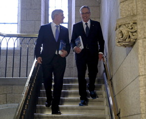 Canada's PM Harper and Finance Minister Oliver walk to the House of Commons to deliver the federal budget in Ottawa