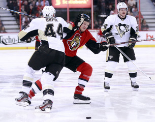 Ottawa Senators' Neil loses the puck between Pittsburgh Penguins' Orpik and Cooke during the second period of their NHL hockey game in Ottawa