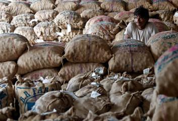 A labourer sits amongst sacks of unsold potatoes at a wholesale market in Manchar village