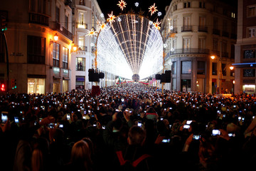 People use mobile phones to take pictures as Christmas lights are turned on to mark the start of the Christmas season at Marques de Larios street in downtown Malaga