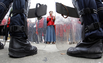 """Riot police stand guard as anti-government """"red shirt"""" protesters gather outside the SC Park hotel in Bangkok"""