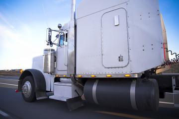 Big white classic powerful rig semi-truck 18-wheler driving highway