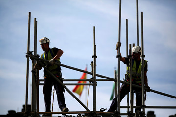 FIle photo of workers building a pipe structure on a scaffolding during the World Day for Safety and Health at Work in the Andalusian capital of Seville