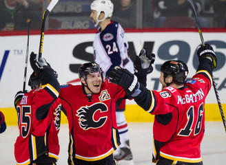 Calgary Flames' Begin and Cammalleri congratulate McGrattan on his goal against the Columbus Blue Jackets during their NHL  game in Calgary