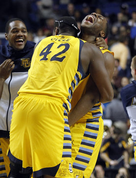 Marquette University's Chris Otule celebrates with Davante Gardner after defeating Butler University during in their third round NCAA basketball game at Rupp Arena in Lexington,