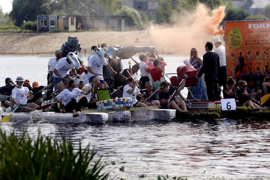 People navigate along the Lielupe river as they participate in the Milk Carton Boat Race in Jelgava